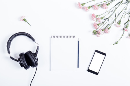 Top view of smart phone, headphones, paper notebook, pencil and flowers lie on white table