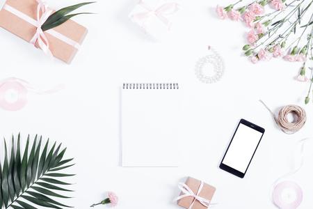 Feestelijke samenstelling: dozen met geschenken, linten, bloemen, juwelen, mobiele telefoon en papier notitieboekje, bovenaanzicht Stockfoto