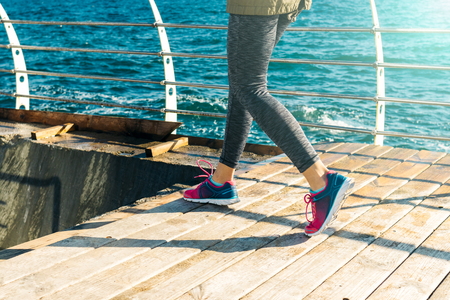 run down: Female legs in sneakers run down the stairs on the beach in the morning, close-up Stock Photo