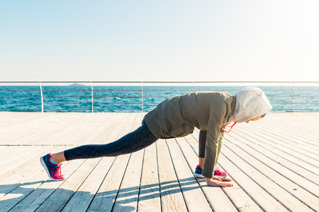 Woman in jacket and hood doing stretching on beach in the morning, wide angle