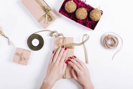 Female hands packing gifts on white background, top view