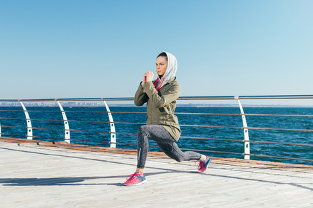 Woman in the jacket and the hood is doing lunges on the beach, wide angle