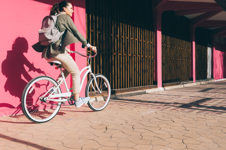 Smiling girl on a Bicycle rides along a pink wall in Sunny day