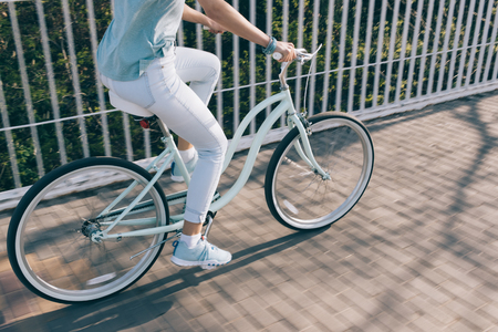 Sportswoman rides fast on a cruise bike around the city in the summer
