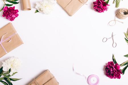 Feestelijke samenstelling van pioenen en giften op een witte lijst, hoogste mening