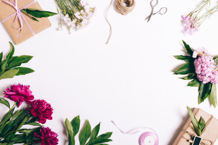 Festive composition of flowers, gifts and ribbons on a white table, top view