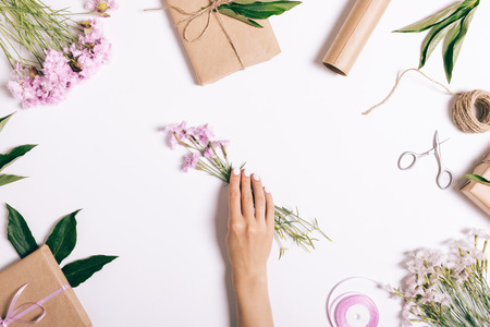 Female hand puts a bouquet of pink flowers on the table, top view