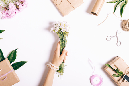 マニキュアと女性の手は、白いテーブルにピンク カーネーションの小さな花束を保持します。平面図、休日のための準備です。