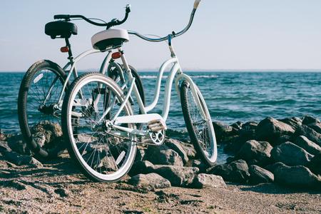 晴れた日の青い海とビーチの 2 つのレトロな自転車 写真素材