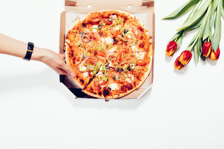 Top view of female hand takes a slice of pizza out of the box. Food and flowers lie on a white table.