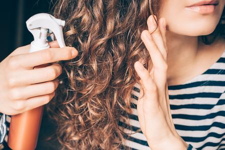 Woman applying spray on curly brown hair close-up Standard-Bild
