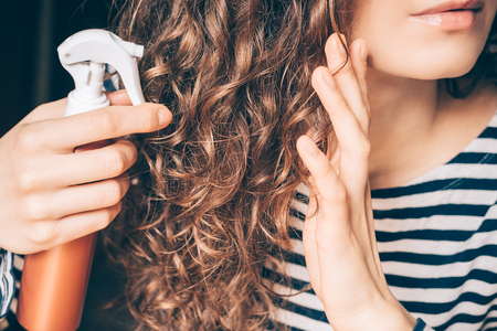 Woman applying spray on curly brown hair close-up Stock Photo