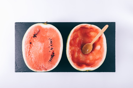 ocas: Sliced ripe watermelon on white table and wooden spoon top view Foto de archivo