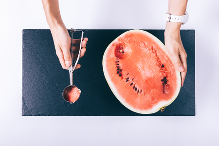 table top: Women hands sliced watermelon spoon on white table top view