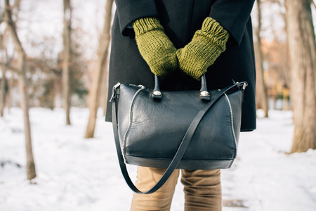 winter fashion: Cropped image of a woman in a coat holding her purse in hands outdoors in winter