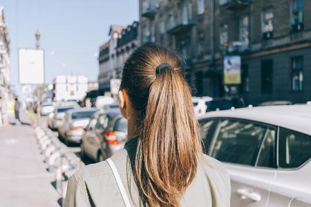 夏に都市を通って歩いて茶色の髪の少女の後ろから表示します。