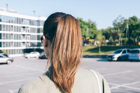 Close-up van een brunette die door de stad in de zomer loopt, uitzicht vanaf achterkant Stockfoto