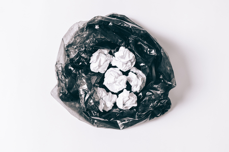 Garbage bag with crumpled pieces of paper on a white background top view Standard-Bild