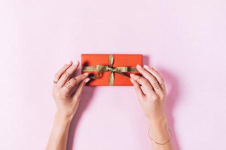 Hoogste mening van vrouwelijke handen die een boog op een doos met een gift op een roze achtergrond binden Stockfoto