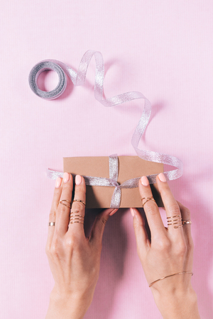 Top view of womens hands tying a bow on a gift box