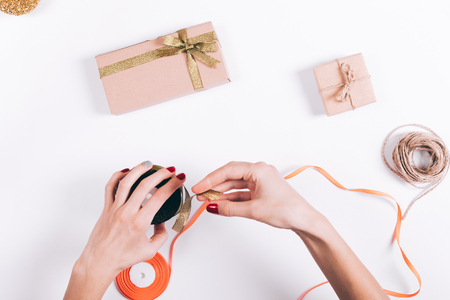 Womens hands tying the ribbon on the box with gifts on a white table top view