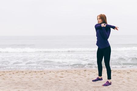 Giovane donna dai capelli rossi che fa sport sulla spiaggia Archivio Fotografico