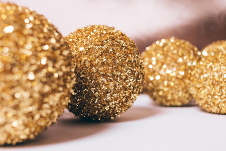 Close-up of yellow Christmas balls on white table Foto de archivo