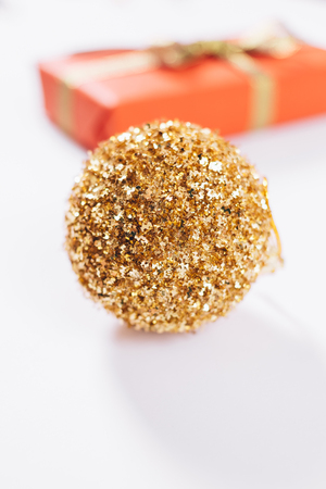 Golden christmas ball and box with gift on white table, vertical framing Stock Photo