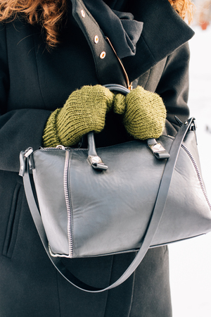 Woman in a black coat and green mittens holding a handbag, a vertical framing 스톡 콘텐츠