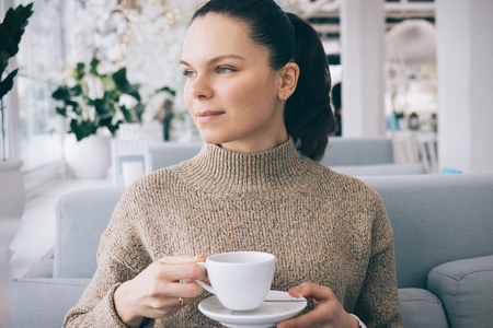 Young woman with brown hair in a sweater drinking tea at a restaurant