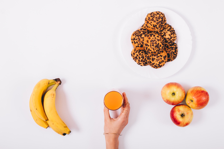 Glass of orange juice in a female hand, a banana, an apple and a plate with cookies on a white table top view