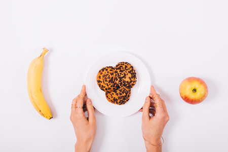 Plate with cookies in female hands, a banana and an apple on a white table top view