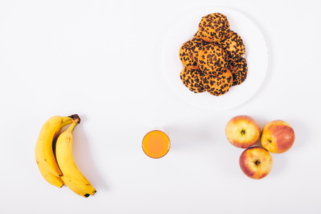 Apple, banana, plate of cookies and orange juice in a glass on a white table top view Stock Photo