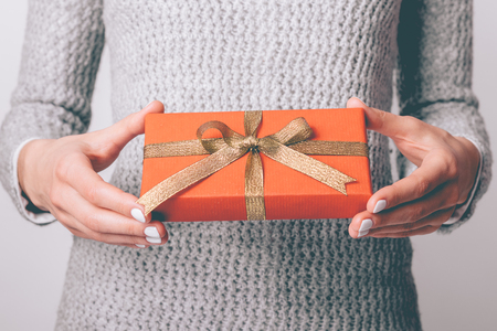 Gift box in red wrapping paper with golden ribbon in female hands close-up Foto de archivo