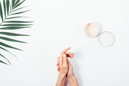 Mujer frotando crema en la piel de las manos sobre una vista superior de fondo blanco