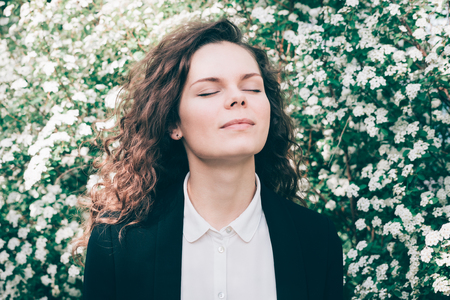 Portrait of a beautiful young woman with closed eyes on a spring flowers background
