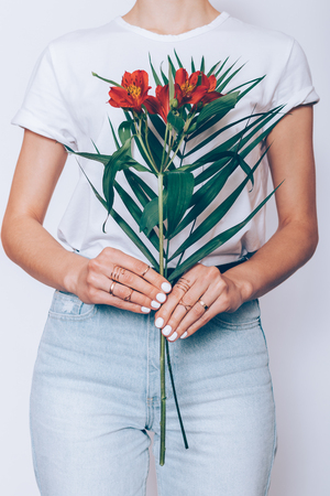 Slender woman holding a bouquet of red flowers in hands with a manicure on a white background, vertical cropping