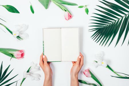 Flower arrangement and an open book in female hands on a white table top view