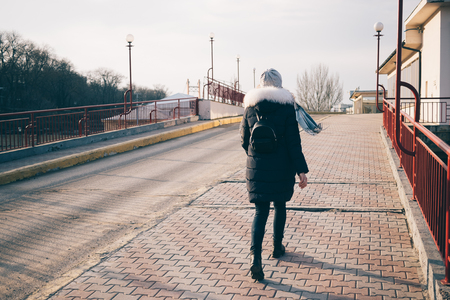 Full length rear view of a young woman in down jacket, hat and small backpack vigorously walking on a spacious street. Shining winter sun, her scarf fluttering in the wind.
