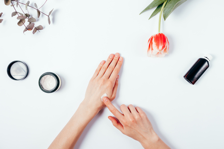 Woman's hands apply cream on skin. The concept of pre-testing cosmetics before use. Top view of female hands among the feminine environment: tulip flower, eucalyptus branch, lotion and cream. Flat lay composition on white background.
