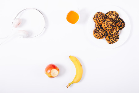 Top view breakfast or snack. Healthy snacks: cookies, cup of juice, apple and banana on white background. Flat lay composition.