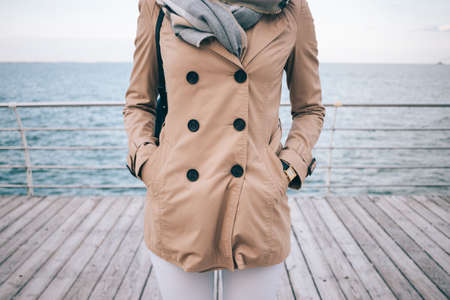 Spring marine outfit. Fashionable girl standing on the waterfront. Cropped photo of slender young woman wearing beige trench coat, large scarf and gold wrist watches. Sea on the background.