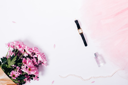 Flat lay frame made of pink flowers bouquet, tulle skirt, gold wrist watches, pearls and bottle of perfume. Top view festive composition of feminine details to prepare for party on white background.