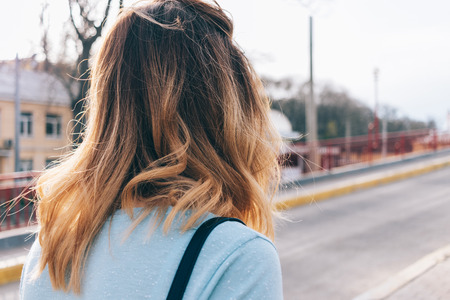 The back of the head of a young woman walking down the street. Close-up hurrying girl with disheveled wavy hair. Imagens