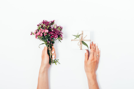 Womans hands holding small bouquet and tiny gift box tied with jute rope. Flat lay composition with pink flowers and present on white background.