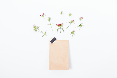 Top view of the paper bag with the badge in the center of a white table. Spring flat lay composition of gift package with little pink flowers above it.