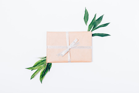 Top view of gift box wrapped in kraft paper with a silver ribbon bow, decorated with green leaves in the center of flat lay composition on a white background. Stock Photo