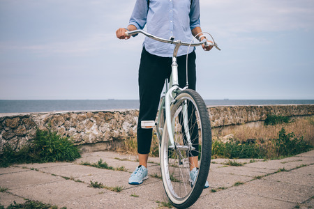 Unrecognizable young female in casual outfit standing next to her cruiser bicycle holding handlebar. Close-up of woman on bike ride near the sea.