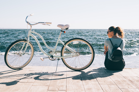 Stylish young woman sitting at the background of blue sea looking at her shiny cruiser bicycle. Female wearing backpack and casual outfit resting after bike ride at sunny summer day.