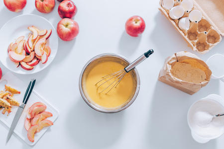 Ingredients and tools for cooking apple pie, top view. Metal bowl filled with batter, whisk, cut fruits, eggshells, flour and sugar, flat lay composition on kitchen white table.